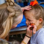 Woman face painting little girl.