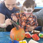 Woman helping little boy paint pumpkin