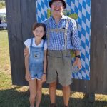 Father and daughter dressed for Oktoberfest posing against Oktoberfest background.