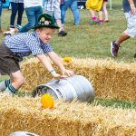Little boy dressed for Oktoberfest keg rolling