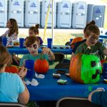 Kids paintin pumpkins under tent at Carbon County Oktoberfest