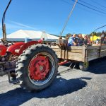 Red tractor pulling hay wagon with crowd of people