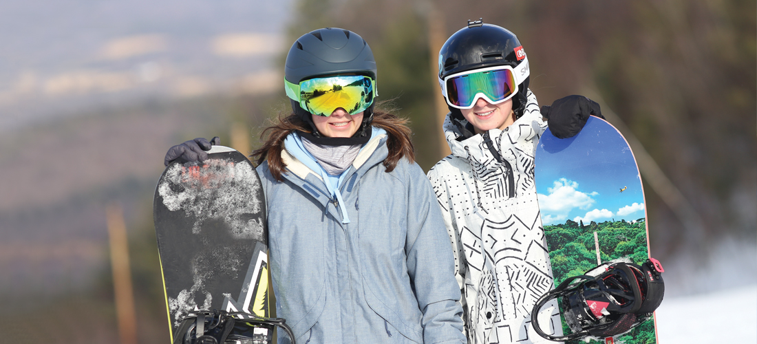 Two girls with goggles on and holding snowboards.