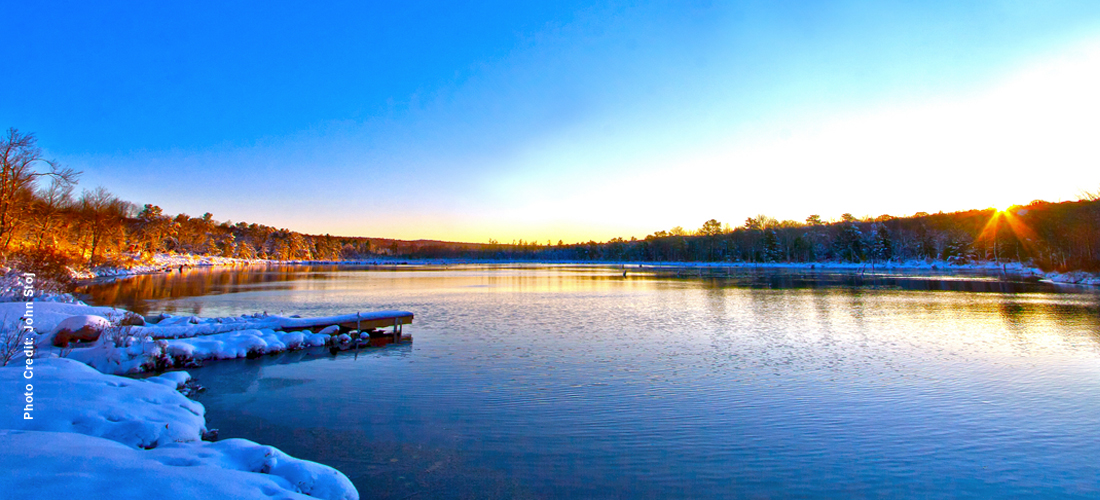 Sunrise at Carbon County lake in winter with snow on ground.