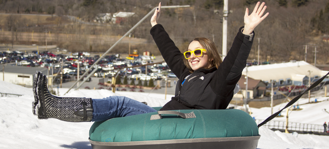 Woman tubing at ski resort.
