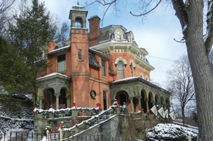 Three-quarter view of Harry Packer Mansion, Jim Thorpe, PA in winter with snow around building.
