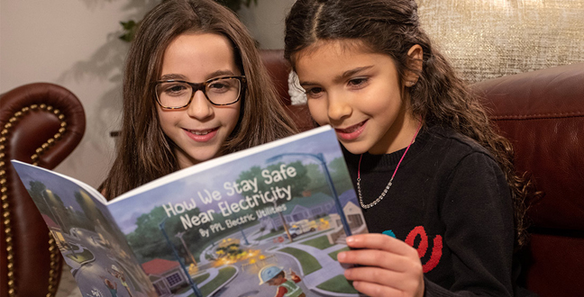Two young girls sitting on couch reading How We Stay Safe Near Electricity Book/
