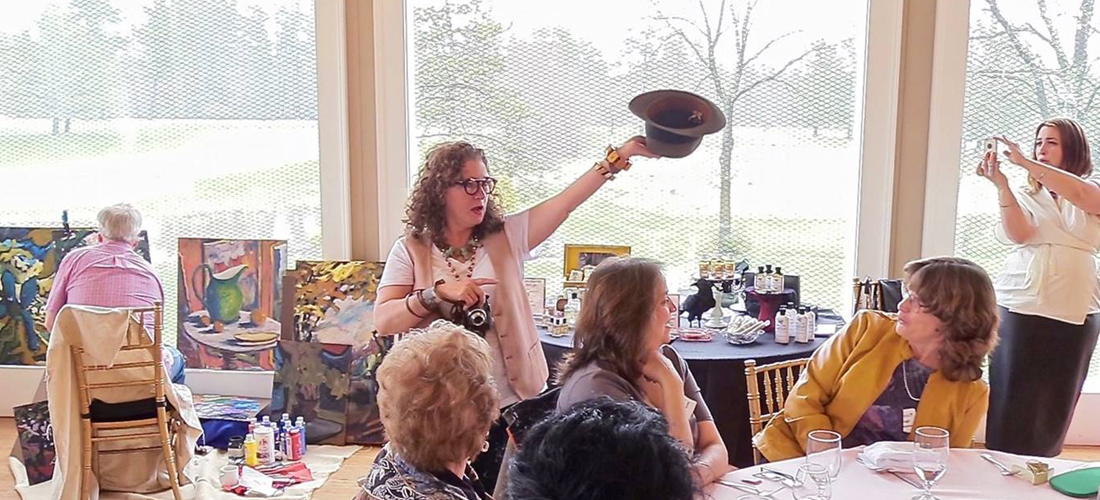 Model taking hat off in front of audience at Administrative Professionals Luncheon