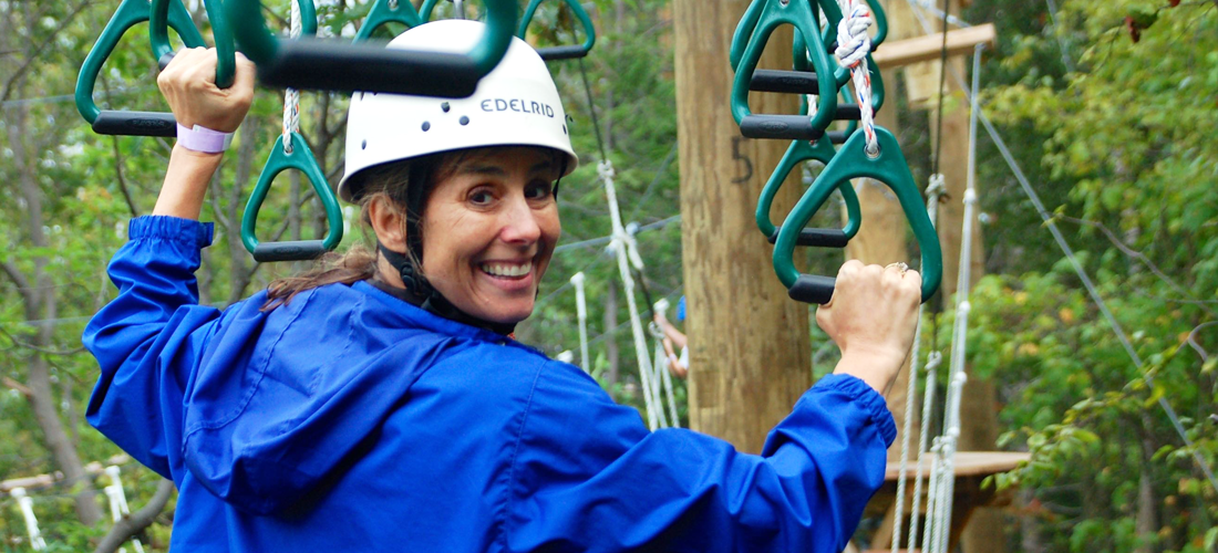Woman in blue jacket smiling and ziplining
