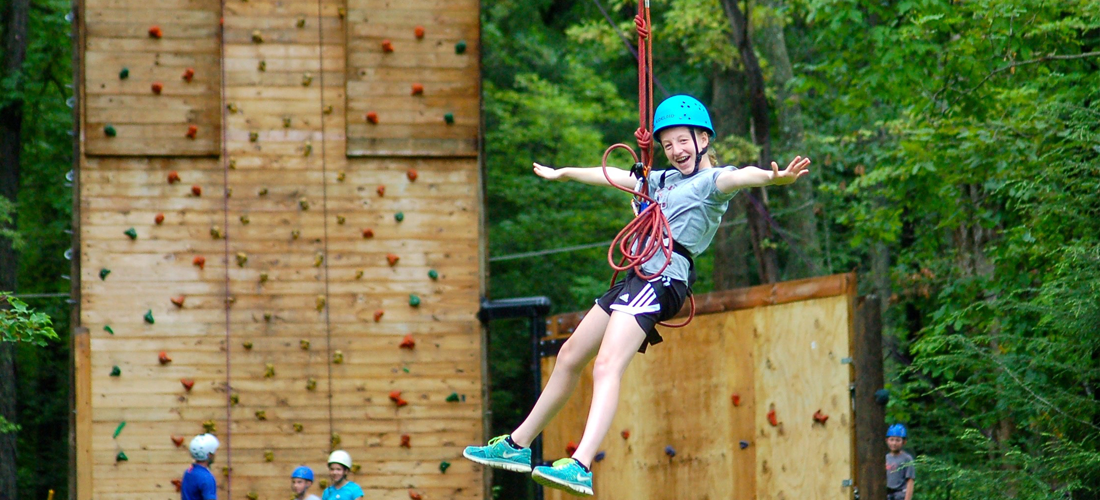 Young girl ziplining with rock climbing wall behind her