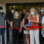 Woman cuts red ribbon at ribbon cutting