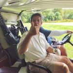 Man in golf cart giving thumbs up