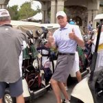 golf carts lined up and male golfer giving thumbs up