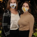 Two business women with masks on posing for a photo