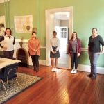 Five women standing in room with green walls and hardwood flooring