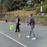 Two women playing tennis on the same side of the net