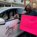 Jenny's Sweets donating to volunteer holding Operation Give a Gobbler sign