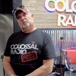 Doc standing in front of Colossal Radio Sign