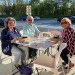 Maureen Donovan, Linda Rex and Kathy Henderson sitting at table outside