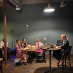 woman alone at table reading to other women at tables