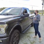 Kylie distributing movie tickets to man in pick up truck