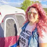 Pink haired woman in front of camping tent