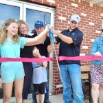 Owners of Shoenberger's Meat Market with scissors cutting red ribbon
