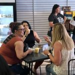 Crowd of ladies sitting at table talking at Wine & More on 1st ribbon cutting