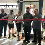 Owner cutting red ribbon with staff at Wine & More on 1st ribbon cutting