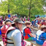 crowd of people with life jackets getting instructions by water