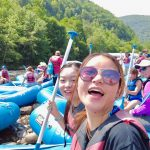 Two asian women on rafts smiling