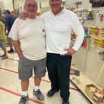 Two gentlemen posing for photo inside store