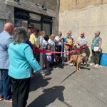 Ribbon cutting ceremony outside with guests and dogs