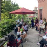 Guests sitting on patio of Harry Packer Mansion