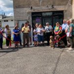 Owners cutting red ribbon at ribbon cutting