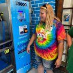 Woman next to dog wash automated machine