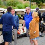 Four golfers talking by golf carts