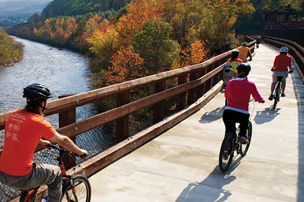 Bikers on D&L trail overlooking river in fall