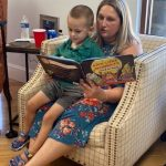 Woman reading a book to child on her lap