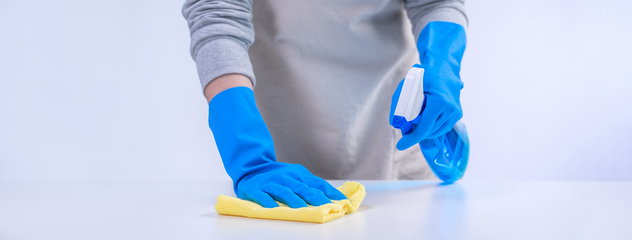 Young woman housekeeper in apron is cleaning, wiping down table surface with blue gloves, wet yellow rag, spraying bottle cleaner, closeup design concept.