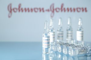 Johnson and Johnson vaccine against COVID-19. Glass medical vials with liquid on the background Jonson & Jonson company logo. Ampoules with coronavirus vaccine on a medical glass table