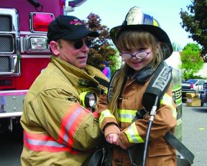 firefighter in gear with child wearing firemans hat