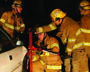 2 fireman in training using equipment on a car
