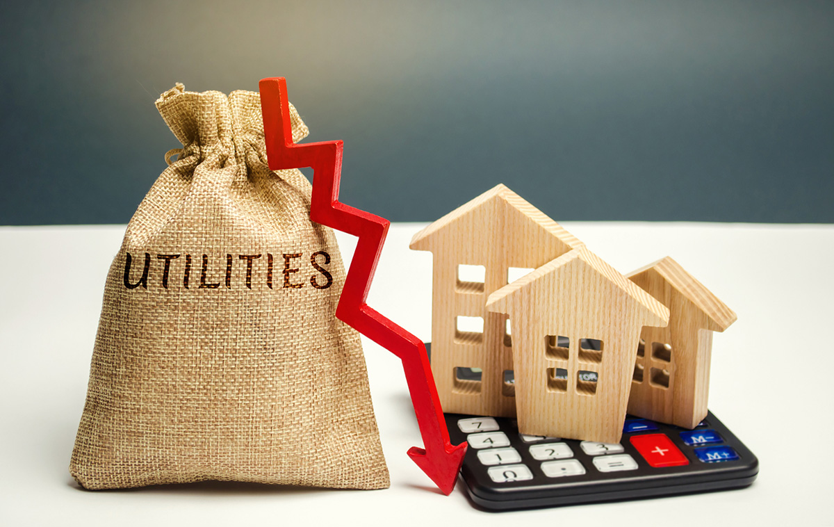 Money bag with the word Utilities and an arrow down and wooden houses on the calculator. Reduced prices for utilities. Low prices for electricity, heating. Payment for the use of water.