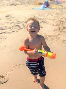 Smiling Child On Beach Watergun