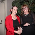 Carm O'Grady accepting congratulations on her Employee of the Year award from President Joanne Sorensen