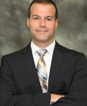 headshot, male, middle age. black short hair, dark suit, gold and blue stripped tie