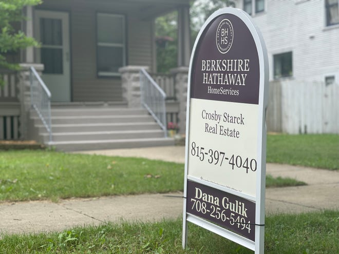 realtor yard sign in front of brick house
