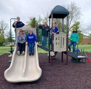 five adults on plastic playground equipment