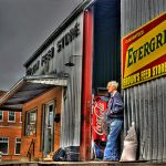 elderly man leaning against old metal building - Brown's Feed Store
